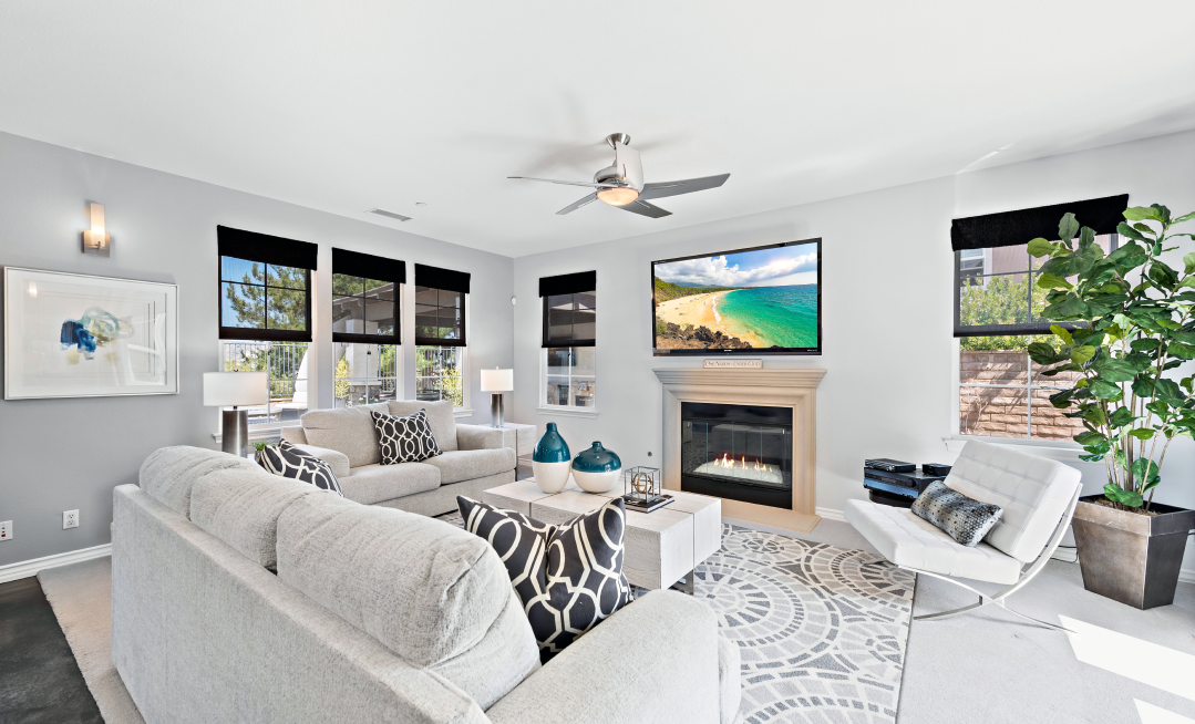 The interior of an Orange County home. Coaches and chairs are gathered around a fireplace with a TV above the mantle.