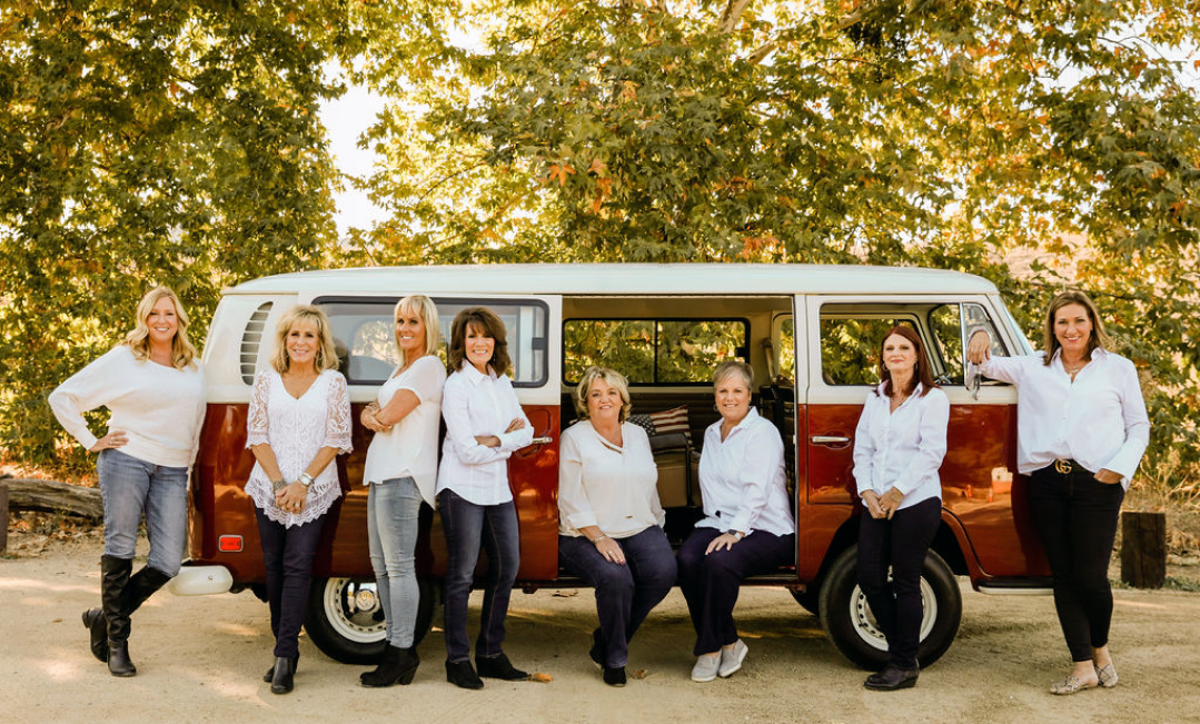 The Coast to Canyon team pose smiling in front of a classic van, all wearing white tops paired with jeans of black slacks.