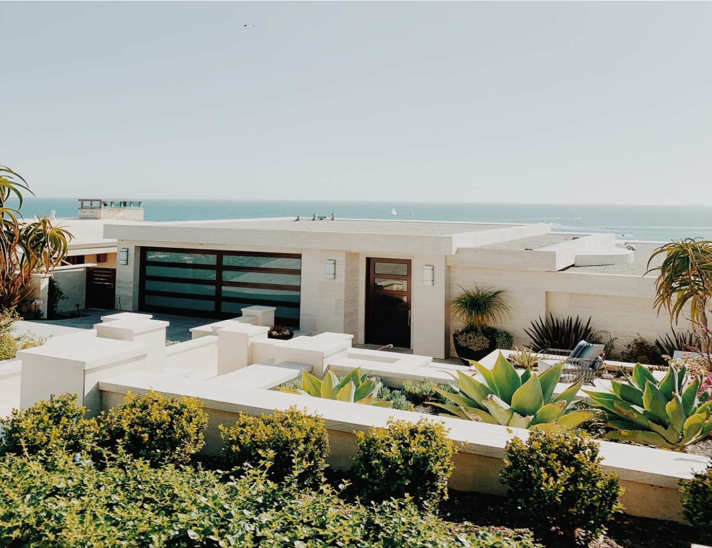 The exterior of a modern home in Orange County. The ocean is in the distance and the property has a number of coastal plants